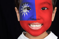 Asian chinese little girl with Taiwan flag on face. Asian chinese little girl with Taiwan flag on the face in isolated black background stock photo
