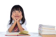 Asian Chinese little girl thinking while reading Royalty Free Stock Photos