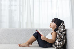 Asian Chinese little girl thinking while reading on the sofa Royalty Free Stock Photos