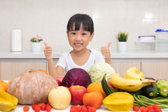 Asian Chinese little girl thumbs up with fruit and vegetable stock photos