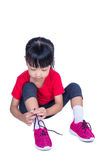 Asian Chinese little girl tying her shoes. In isolated white background Royalty Free Stock Photos