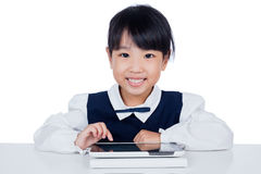 Asian Chinese little girl in uniform playing with tablet compute Stock Images