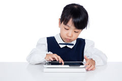 Asian Chinese little girl in uniform playing with tablet compute Stock Photo