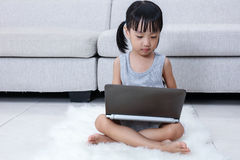 Asian Chinese little girl using laptop on the floor Stock Photography