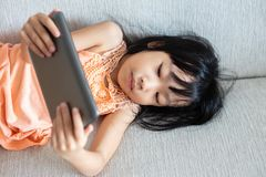 Asian Chinese little girl using tablet lying on the sofa. In the living room Royalty Free Stock Photos