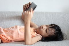 Asian Chinese little girl using tablet lying on the sofa. In the living room Stock Photo