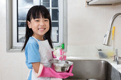 Asian Chinese little girl washing dishes in the kitchen. At home Royalty Free Stock Images