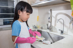 Asian Chinese little girl washing dishes in the kitchen. At home Stock Photography