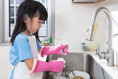Asian Chinese little girl washing dishes in the kitchen Royalty Free Stock Photo