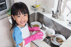 Asian Chinese little girl washing dishes in the kitchen. At home Stock Image