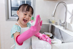 Asian Chinese little girl washing dishes in the kitchen Royalty Free Stock Image