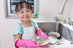 Asian Chinese little girl washing dishes in the kitchen Stock Images