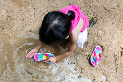 Asian Chinese little girl washing sandals at riverbank Stock Photography
