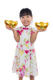 Asian Chinese little girl wearing cheongsam holding gold ingot Stock Photography