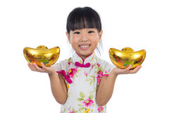 Asian Chinese little girl wearing cheongsam holding gold ingot Royalty Free Stock Photos
