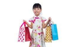 Asian Chinese little girl wearing cheongsam holding shopping bag Royalty Free Stock Photo