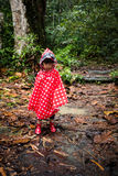 Asian Chinese little girl wearing raincoat in the forest Stock Photos