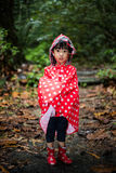 Asian Chinese little girl wearing raincoat in the forest Royalty Free Stock Photography