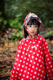 Asian Chinese little girl wearing raincoat in the forest Stock Photography