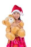 Asian Chinese little girl wearing santa hat holding teddy bear Stock Photo