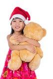 Asian Chinese little girl wearing santa hat holding teddy bear Royalty Free Stock Photo
