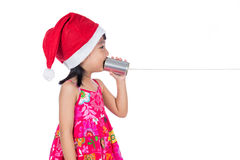 Asian Chinese little girl wearing santa hat holding tin can Royalty Free Stock Photos