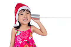 Asian Chinese little girl wearing santa hat holding tin can Stock Photography