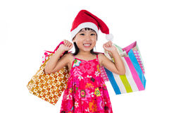 Asian Chinese little girl wearing santa hat with shopping bag Royalty Free Stock Photos