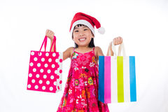Asian Chinese little girl wearing santa hat with shopping bag Stock Photography