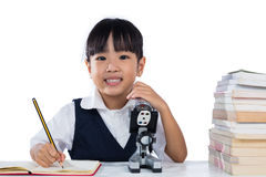 Asian Chinese little girl wearing school uniform with microscope Stock Image