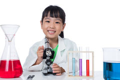 Asian Chinese little girl working with microscope Royalty Free Stock Image