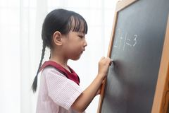 Asian Chinese little girl writing on blackboard. In isolated white background Stock Photo