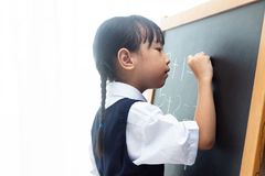 Asian Chinese little girl writing on blackboard. In isolated white background Stock Image