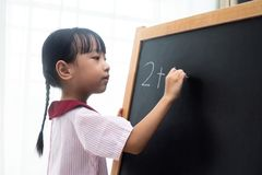 Asian Chinese little girl writing on blackboard. In isolated white background Royalty Free Stock Photos