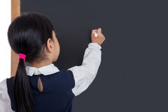 Asian Chinese little girl writing on blackboard. In isolated white background Royalty Free Stock Images