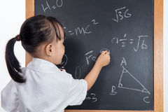 Asian Chinese little girl writing on blackboard. In isolated white background Stock Photography