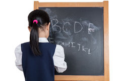 Asian Chinese little girl writing on blackboard. In  white background Stock Images