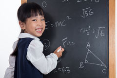 Asian Chinese little girl writing on blackboard. In  white background Stock Photo