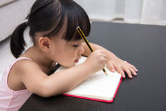 Asian Chinese little girl writing on exercise book Royalty Free Stock Photography