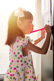 Asian Chinese little girl writing on paper with  back lighting Royalty Free Stock Photo