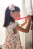 Asian Chinese little girl writing on paper with  back lighting Royalty Free Stock Photos