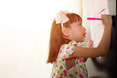 Asian Chinese little girl writing on paper with  back lighting Stock Images
