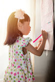 Asian Chinese little girl writing on paper with  back lighting Stock Photos