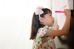 Asian Chinese little girl writing on paper with  back lighting Royalty Free Stock Image
