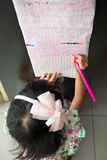 Asian Chinese little girl writing on paper in the morning Royalty Free Stock Photos