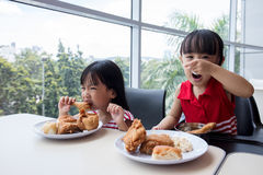 Asian Chinese little girls eating fried chicken Royalty Free Stock Photography