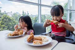 Asian Chinese little girls eating fried chicken Stock Photo