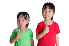Asian Chinese little girls eating sausage. In isolated white background royalty free stock images