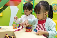 Asian Chinese little girls playing colorful magnet plastic block. S kit at indoor playground Royalty Free Stock Photo