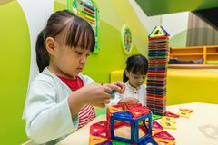 Asian Chinese little girls playing colorful magnet plastic block. S kit at indoor playground Royalty Free Stock Photography
